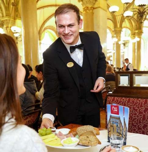 Ein lächelnder Ober serviert einer Dame Frühstück im Café Central