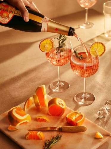 zwei hübsch dekorierte Gläser in die aus der Flasche Chandon Garden Spritz eingeschenkt wird, davor ein Schneidbrett mit Messer und Orangenscheiben