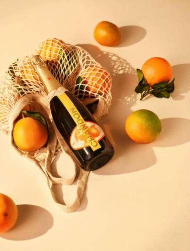 Eine Flasche Chandon Garden Spritz zwischen ganzen Orangen