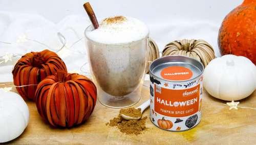 Ein Glas Pumpkin Latte und eine Dose BIO Halloween Pumpkin Spice Latte umgeben von Kürbissen