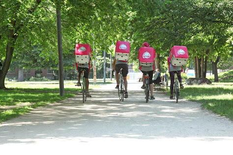 4 FAhrradboten mit rosa Foodora-Rucksäcken fahren in einem Park in Blickrichtung davon