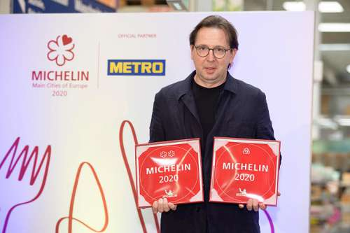Heinz Reitbauer mit der 2-Sterne Plakette fürs Steirereck und dem Bib für die Meierei