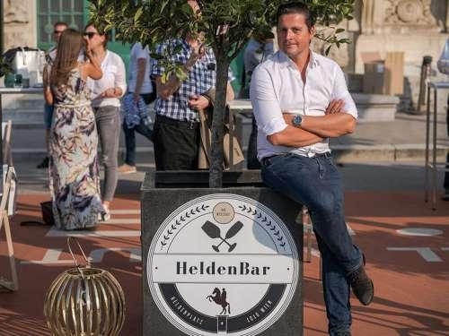 Paul Rittenauer lehnt lässig an einem Baumcontainer mit Heldenbar Logo, dahinter Gäste