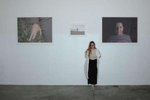Die Künstlerin Ela Sattler vor einer weissen Wand, links und revhts von ihr ist je ein Druck zu sehen