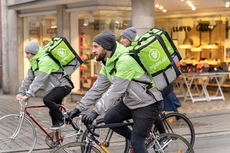 3 Fahrradboten mit grünen Mjam-Rucksäcken fahren in der Stadt