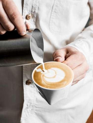 Ein Barista giesst aufgeschäumte Milch zum Espresso und erzeugt damit ein hübsches Muster auf der Oberfläche