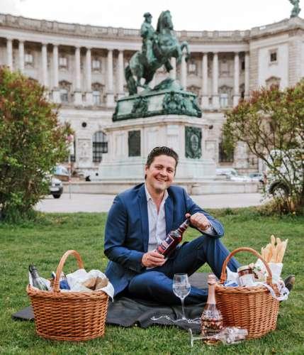Paul Rittenauer auf einer Decke in der Wiese vor dem Reiterdenkmal am Heldenplatz, vor ihm 2 Picknickkörbe, in der Hand eine Flasche Spritz Select