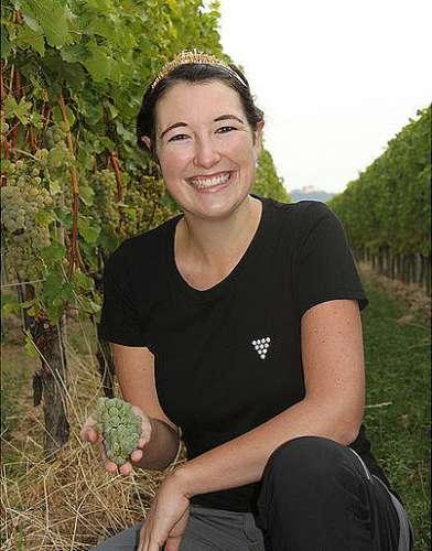 Die Pfälzische Weinkönigin Anna-Maria Löffler vor Weinstöcken mit einer perfekt reifen Weissweintraube in der Hand