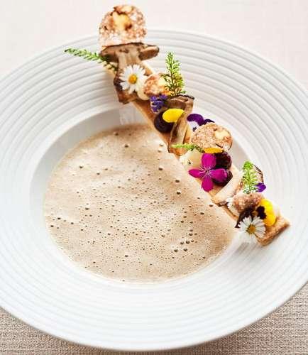 Ein Teller Steinüilzcremesuppe mit bunten Blüten dekoriert