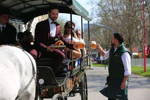 Riding Stelze-Tour durch den Grünen Prater - ein Schweizerhaus-Kellner reicht den Fahrgästen Krügeln Budweiser in den Wagen