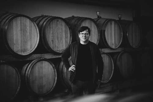 Gerhard J. Wohlmuth im Weinkeller vor 2 Reihen Barriqufässern