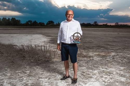 Hans Tschida mit der IWC Auszeichnung auf einer ausgetrockneten Seeufer-Fläche