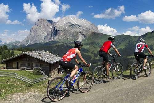 Drei Radfahrer beim  Biken auf der Seiser Alm, im Hintergrund eine Almhütte und schroffe Berge