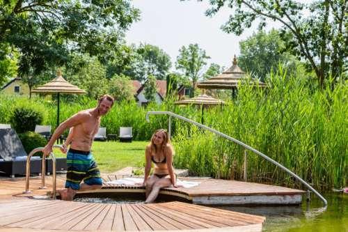 Ein junges Paar geniesst den Sommer am Naturschwimmteich im Villa Vita Pannonia