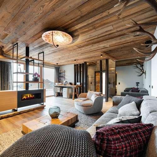 Exklusives Wohnen in luftiger Höhe im Baumhaus Blick über den Kamin zum Fenster, rechts an der Wand Hirschgeweihe
