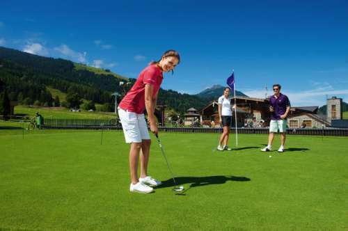 Frau beim Golfen am Putting Green im Sommer