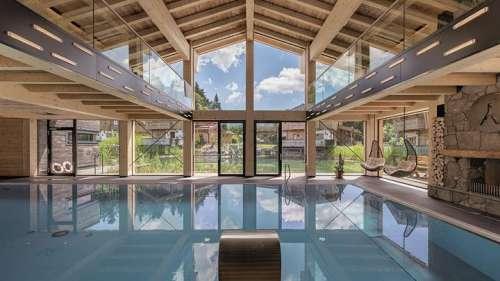 Indoorpool mit Panorama-Lounge im Sommer