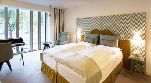 Innenansicht eines Zimmers, Blick übers Bett zum Fenster