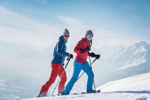 Pärchen beim Schneeschuhwandern vor verschneiter Bergkulisse