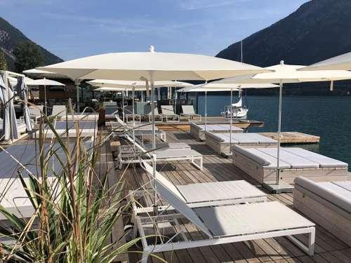 Seebar mit großer Terrasse und hellen Schirmen, dahinter der See und die Alpenlandschaft