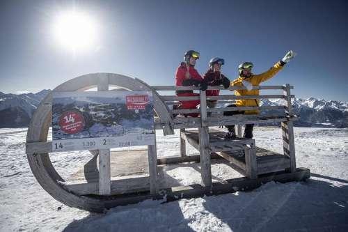 Skifahrer auf großem Schlitten vor herrlich winterlicher Bergkulisse
