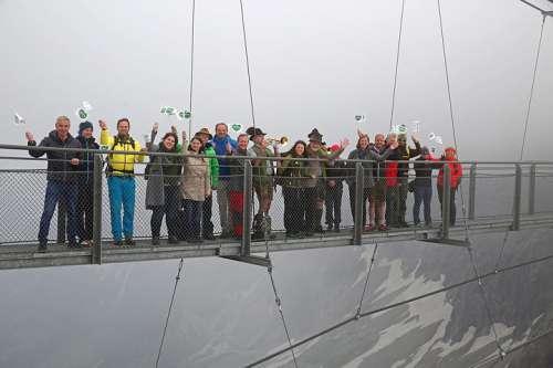 Superwanderer Martina Traisch und Manfred Polansky in der Mitte mit Musikern, Landesrätin Barbara Eibinger-Miedl (re), (li) Erich Neuhold (GF von Steiermark Tourismus) und die Kooperationspartner beim Start am Dachstein auf der Hängebrücke.