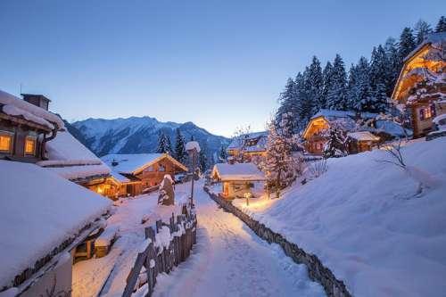Verschneiter Pfad durch das Chaletdorf