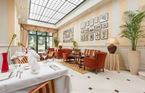 Wintergarten mit gedeckten Tischen im Hotel KAISERHOF Wien