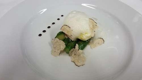 Ein pochiertes Ei von Paolo Parisi auf grünem Spargel, gekrönt mit gehobeltem Trüffel