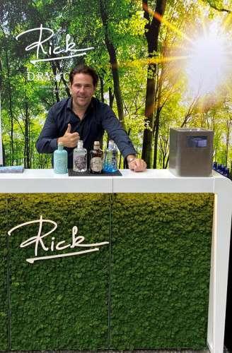 Das Rick Gin Sortiment auf einem weissen Tisch, dahinter Patrick Marchl, im Hintergrund ein Birkenwald