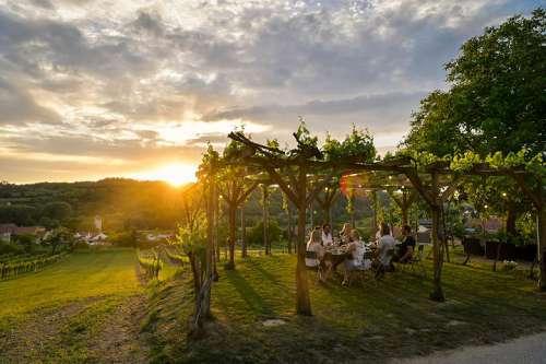 Abenddämmerung, an einem Tisch in einer Laube mitten im Garten verkostet eine Gruppe