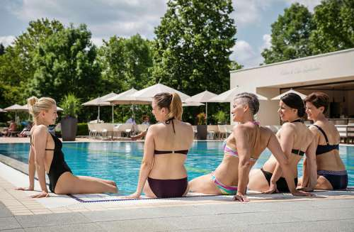 5 Frauen in Bikinis sitzen am Schwimmbadrand mit dem Rücken zur Kamera