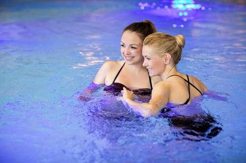 2 junge Frauen im Swimmingpool beim Tratschen