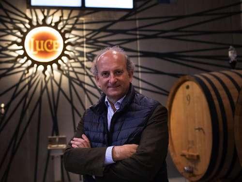 Marchese Lamberto Frescobaldi im Weinkeller, hinter ihm rechts ein Eichenfass, links das imposante Luce-logo